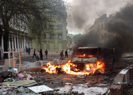 Voiture en flammes dans une rue dévastée.