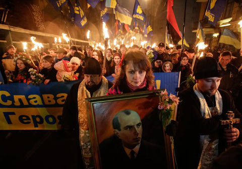 Jeune femme brandissant un portrait de Stepan Bandera.