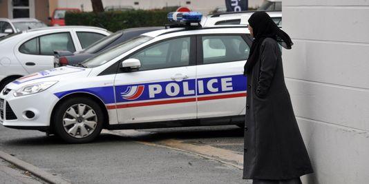 Une femme près d'une voiture de police, aux abords d'une mosquée à La Rochelle, le 9 janvier