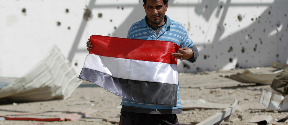 A Yemeni man poses with a national flag at a sports hall that was partially destroyed by Saudi-led air strikes in the Yemeni capital Sanaa on January 19, 2016. / AFP / MOHAMMED HUWAIS