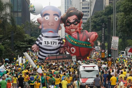 Des manifestants montrent une énorme poupée gonflable à l'effigie de l'ancien président du Brésil Luiz Inacio Lula da Silva en tenue de prisonnier et l'actuelle présidente Dilma Rousseff habillée en voleuse, avec une écharpe où on peut lire