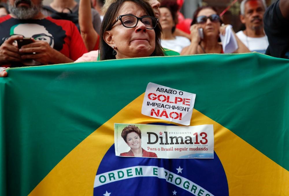 Une manifestante tenant un drapeau avec écrit en portugais sur un autocollant « A bas le coup d'État, non à la destitution » lors d'une manifestation de soutien à la présidente du Brésil Dilma Rousseff et de l'ancien président Luiz Inacio Lula da Silva à Sao Paulo, au Brésil, 31 mars 2016. Photo: Andre Penner/AP