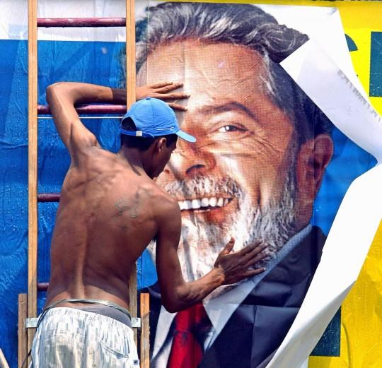Un travailleur colle une affiche de campagne pour le candidat brésilien à la présidence Luiz Inacio Lula da Silva, du Parti des Travailleurs(PT), le 24 octobre 2002, à Sao Paulo, au Brésil. Photo: Marucio Lima/AFP/Getty Images