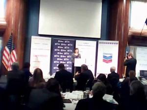 Une capture d'écran de la secrétaire d'État adjointe américaine aux Affaires européennes, Victoria Nuland, parlant à des chefs d'entreprise américains et ukrainiens le 13 décembre 2013, lors d'un événement parrainé par Chevron, dont le logo est à gauche de Nuland. Le sénateur d'Arizona, John McCain, se montre, debout sur la scène, avec des extrémistes de droite du Parti Svoboda, pour dire à la foule que les États-Unis étaient avec eux dans leur contestation du gouvernement ukrainien.