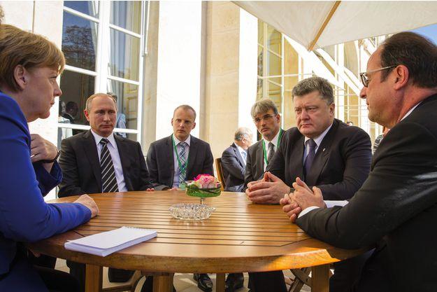 Les dirigeants allemand, russe, ukrainien et français – Angela Merkel, Vladimir Poutine, Petro Porochenko et François Hollande – réunis le 2 octobre 2015 à Paris pour trouver une issue au conflit ukrainien. Une crise qui, selon Alain Juillet, pourrait avoir été « montée de toutes pièces par les néoconservateurs américains ». Reuters