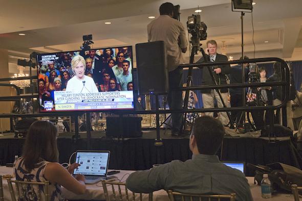 La candidate démocrate à la présidence, Hillary Clinton, sur un écran en train de s'adresser à ses partisans, au moment où les journalistes bouclent leurs articles après une conférence du candidat probable du parti Républicain, Donald Trump, le 7 juin. (Mary Altaffer / AP)