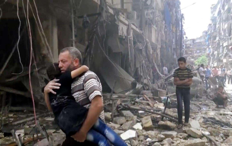 Un homme porte un enfant après des frappes aériennes sur Alep, Syrie, le 28 avril 2016. (Validated UGC via AP video)