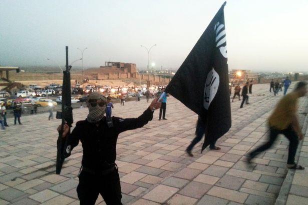 Un combattant de l'État Islamique en Irak et au Levant (EIIL) tient un drapeau de l'EIIL et une arme dans une rue de la ville de Mossoul, le 23 juin 2014 | Reuters