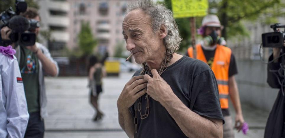 Eric Petetin s'enchaîne symboliquement à l'arrivée de son procès, en mai 2014. (JEFF PACHOUD/AFP)