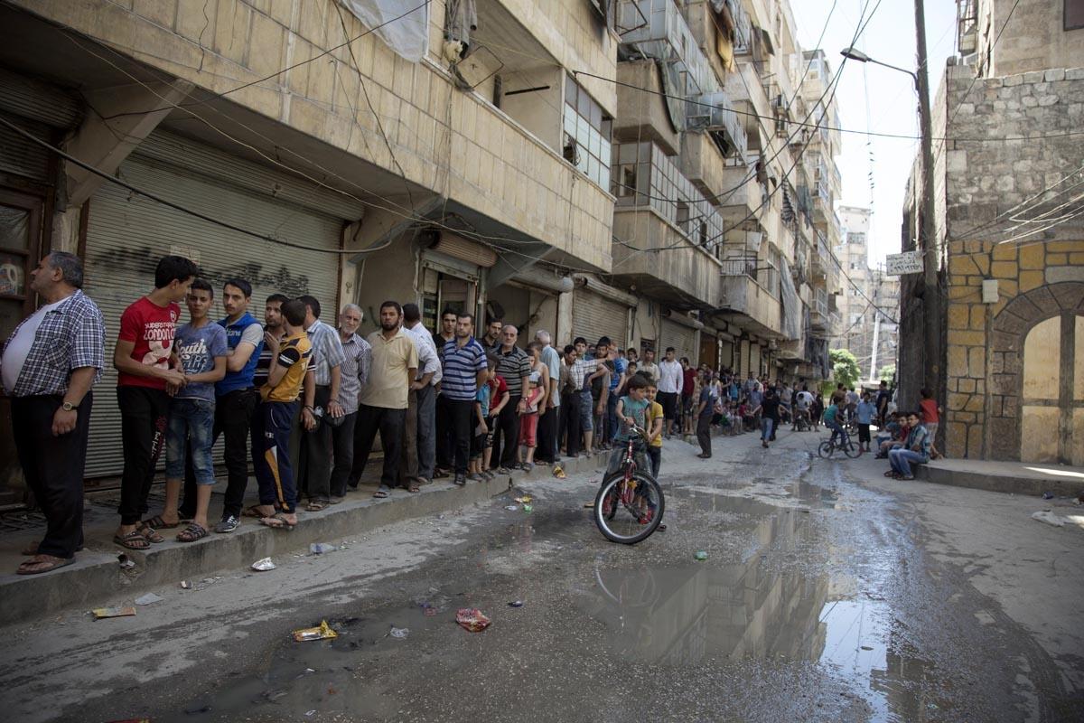 Des habitants d'Alep font la queue pour acheter du pain, en juillet 2016 (AFP / Karam Al-masri)