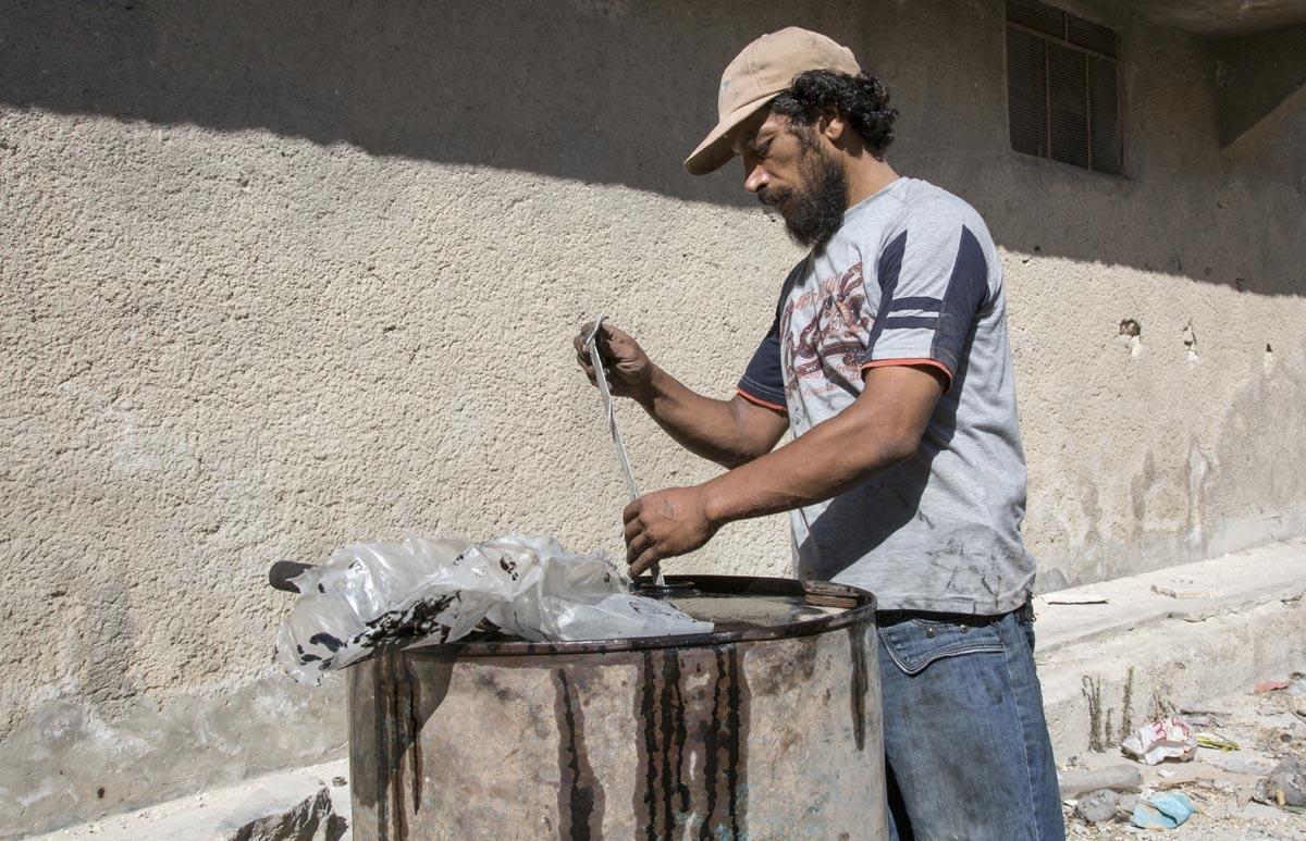 Un Syrien fabrique du carburant de fortune à l'aide de plastic usagé, le 10 septembre 2016 à Alep. Quelques jours plus tard, cet homme sera tué par une explosion accidentelle au cours du processus de raffinage (AFP / Karam Al-masri)