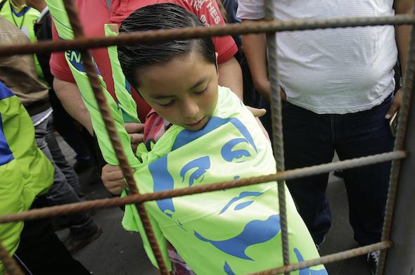 Un garçon brandit un drapeau avec le portrait au pochoir de Rafael Correa, le président de l'Équateur, durant la convention Alianza PAIS à Quito, ce samedi. Correa est le leader du parti. (Dolores Ochoa / AP)