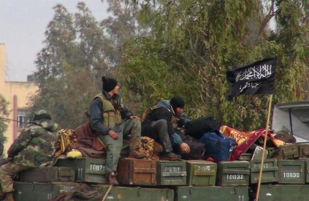 Sur cette photo de 2013, qui a été authentifiée sur la base de son contenu et d'autres rapports de l'Associated Press, des rebelles de l'organisation affiliée à al-Qaïda, Jabhat al-Nosra, sont assis sur un camion chargé de munitions à la base aérienne de Taftanaz, qui a été capturée par les rebelles dans la province d'Idlib dans le Nord de la Syrie. (Edlib News Network/AP)