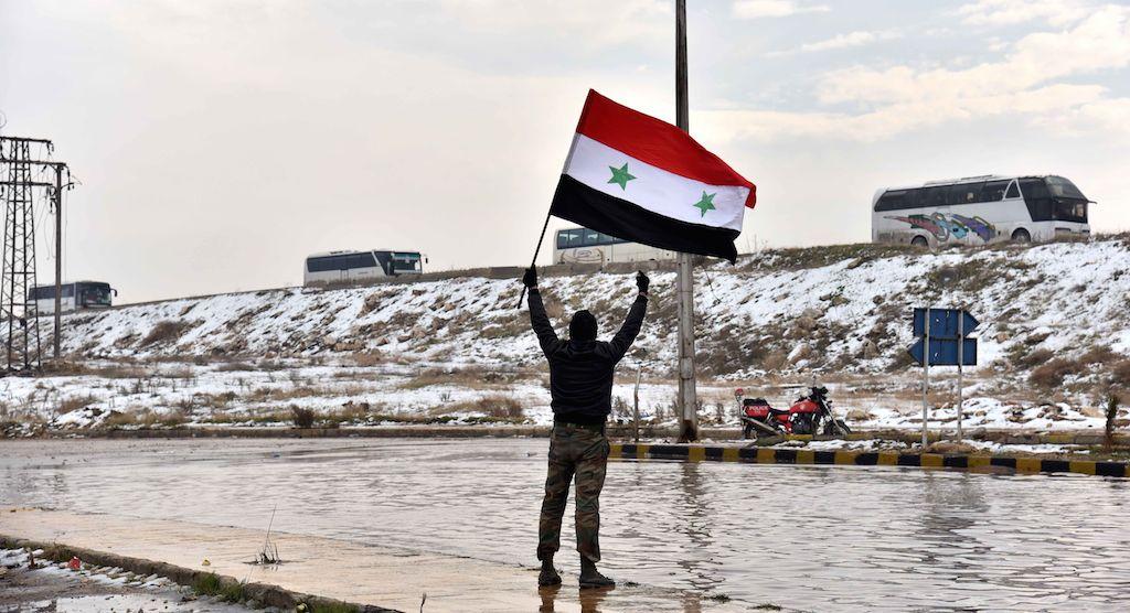 Illustration. Ici, un homme agite un drapeau syrien alors que des membres de l'opposition sont évacués d'Alep dans un convoi - CHINE NOUVELLE/SIPA