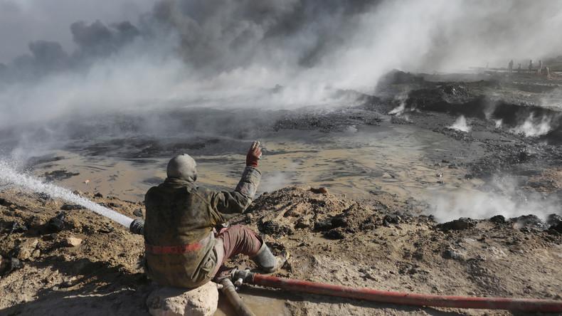 Un employé d'un site pétrolier essaie d'éteindre l'incendie lancé par des combattants de Daesh d'un champs pétrolier à Qayyara, au sud de Mossoul. © Goran Tomasevic Source: Reuters