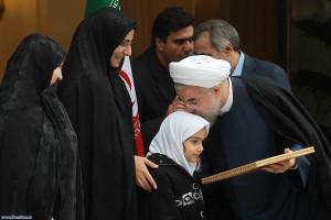 Le 24 novembre 2013, le président iranien Hassan Rouhani célèbre la signature d'un traité provisoire sur le programme nucléaire iranien en embrassant le visage de la fille d'un ingénieur nucléaire iranien assassiné. (Iranian government photo)